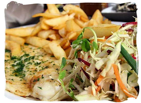 Kingklip with potato chips and salads - seafood cuisine in South Africa.