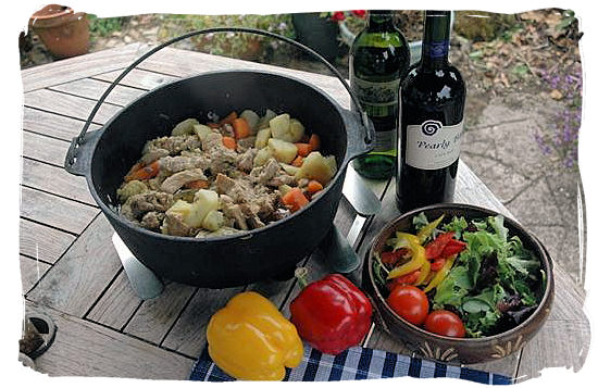 "Delicious ""Potjiekos"" (pot stew), served with salads and accompanied by a good wine - South African traditional food"