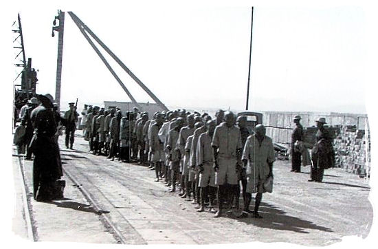 Old prison photo showing prisoners after disembarkation, lined up to enter the prison - Amazing Robben Island tour, visit Nelson Mandela prison cell