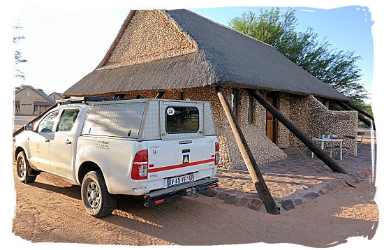 A rented 4x4 Toyota Hilux safari vehicle in front of a chalet in Twee rivieren camp in the Kgalagadi Transfrontier National park