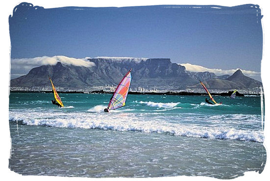 Surfers viewed from Blouberg beach, with Table Mountain as backdrop - Activity Attractions in Cape Town South Africa and the Cape Peninsula