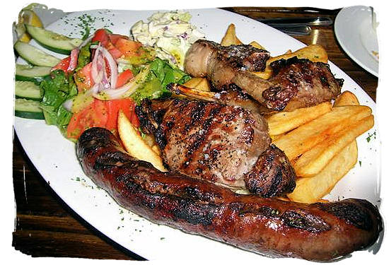 Grilled boerewors (sausage), steak and lamb chops with fried potato chips and salads, typical South African boerekos (farm house cooking) - South African traditional food