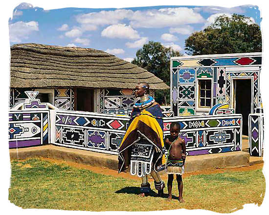 Ndebele women showing off the traditional decoration of her home