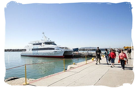 Tourists walking on the Robben Island quayside with the ferry in the background - Amazing Robben Island tour, visit Nelson Mandela prison cell